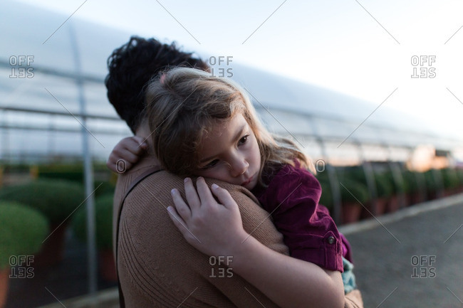 Tired girl carried by mother