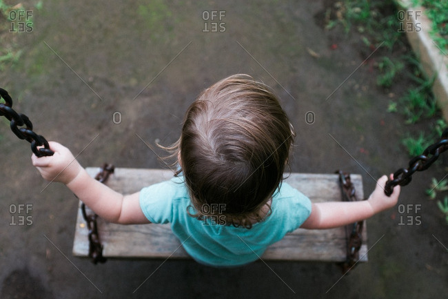 Child swinging on a wooden swing