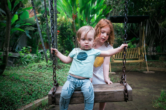 Girl pushing boy on a wooden swing