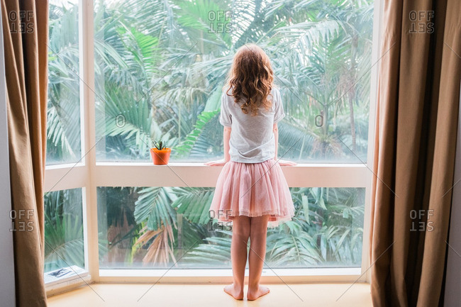 Girl with curly red hair looking out a window at palm trees