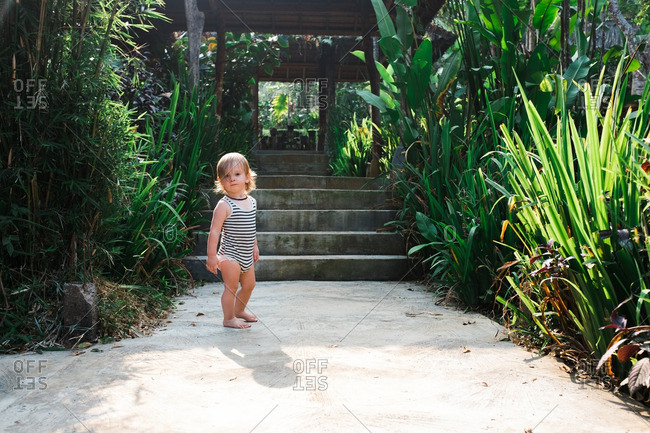 Baby boy standing on path in a tropical garden in West Java, Indonesia