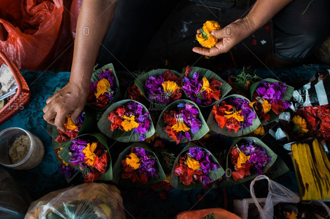 Person making flower offerings in a traditional market in Sanur, Bali, Indonesia