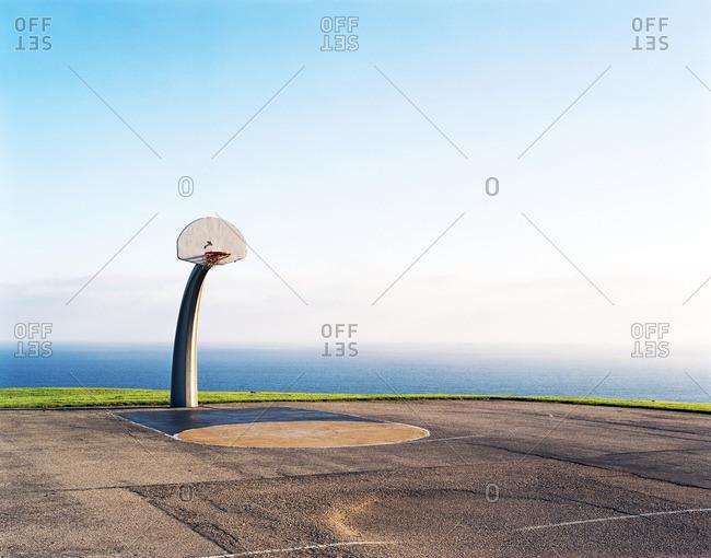 Basketball goal on an outdoor court near the coast