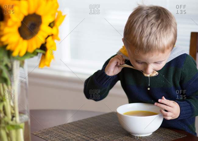 Boy dripping soup as he eats a spoonful