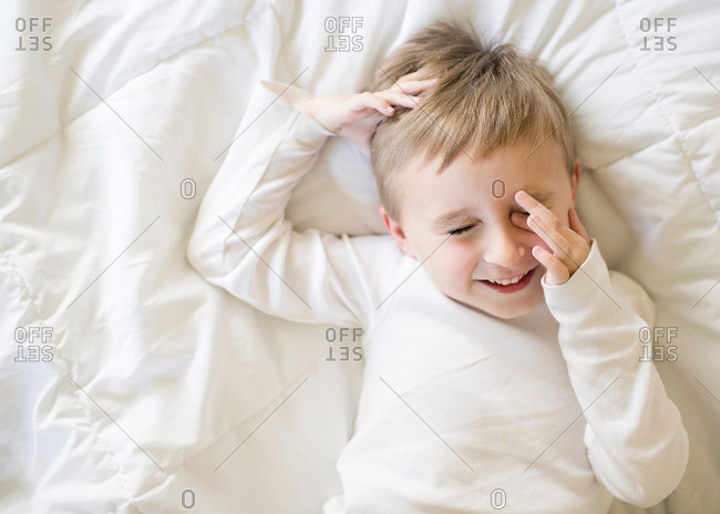 Boy lying on a bed rubbing his eyes and laughing