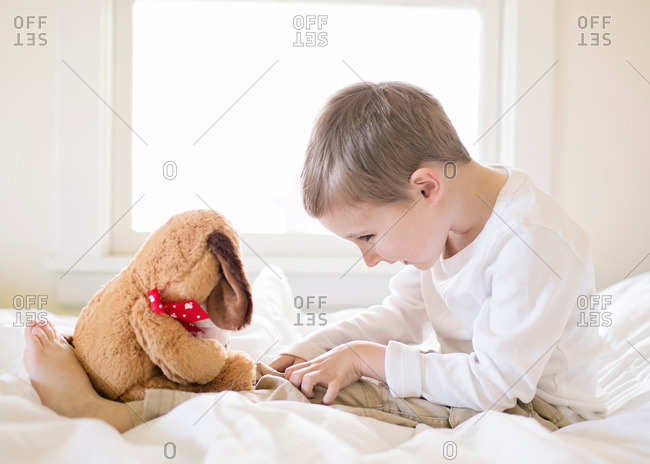 Boy sitting on a bed playing with a stuffed dog