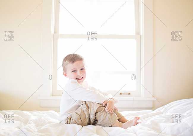 Boy on a bed hugging his knees and smiling