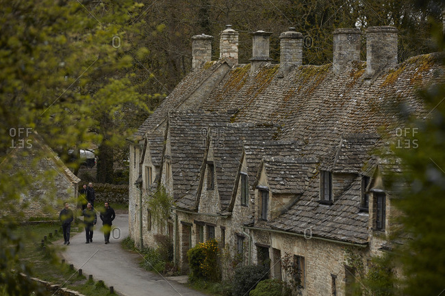 Bibury, England - May 1, 2016: Group of tourists walking through the village of Bibury, England