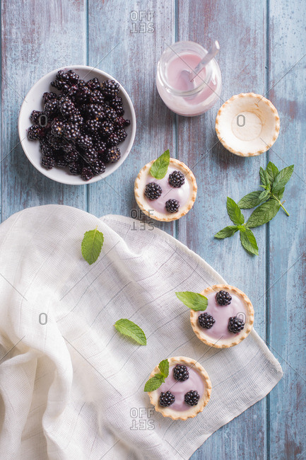 Homemade blackberry pies with bowl of fresh blackberries and jar of yoghurt on wooden background