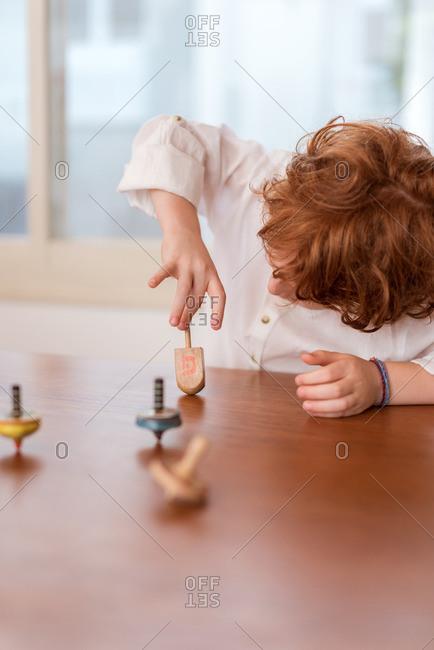 Child spinning a dreidel