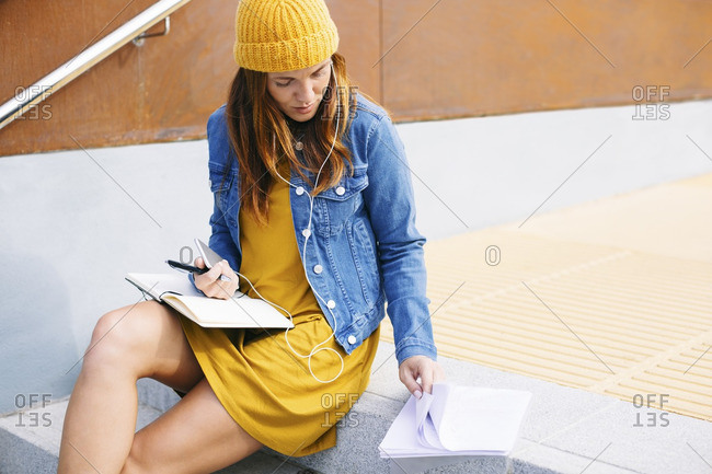 Young woman with notebook sitting on steps
