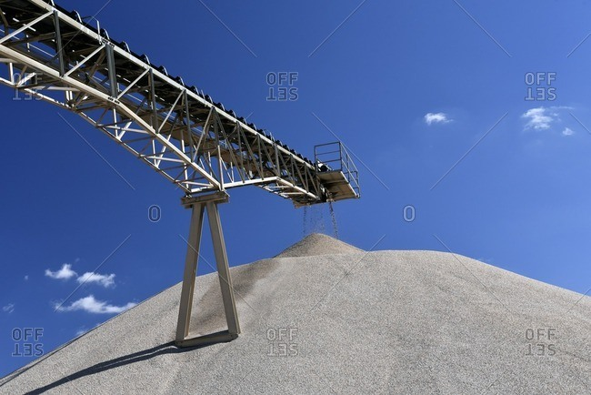 Conveyor belt above heap of gravel in gravel pit