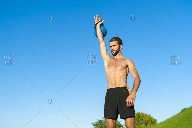 Man exercising with kettlebell under blue sky