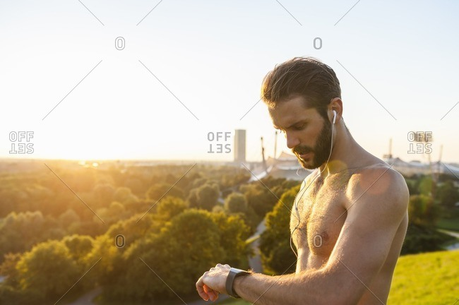 Barechested athlete with earbuds looking on watch at sunset