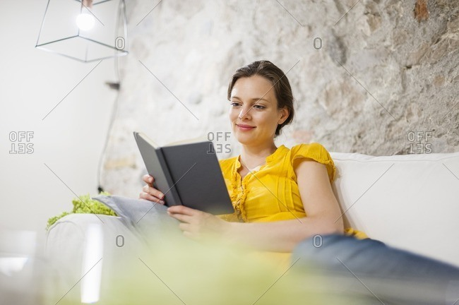 Woman lying on couch, reading a book