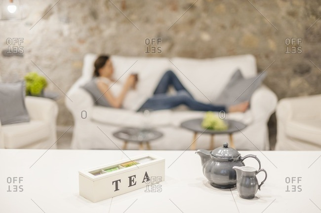 Woman sitting on couch, drinking tea