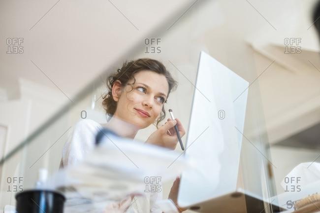Woman at home applying eye makeup