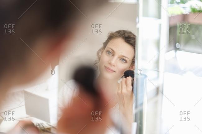 Woman looking in mirror applying eye makeup