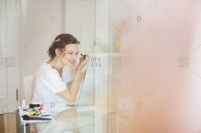 Woman at home applying mascara