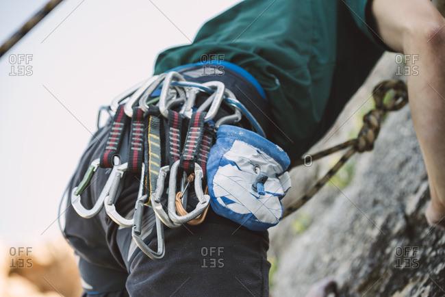 Close-up of magnesium bag and climbing carabiners of man climbing a rock wall