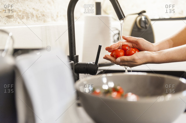 Woman washing tomatoes in kitchen