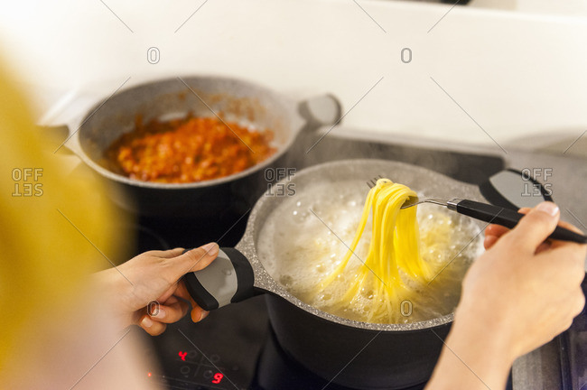 Woman preparing spaghetti, trying if they are ready to eat