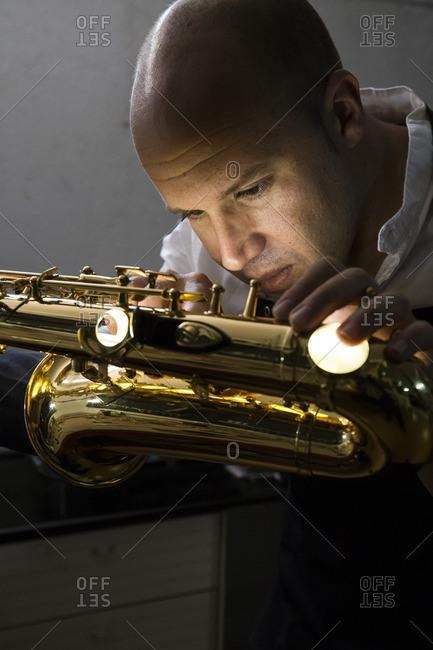 Instrument maker repairing a saxophone