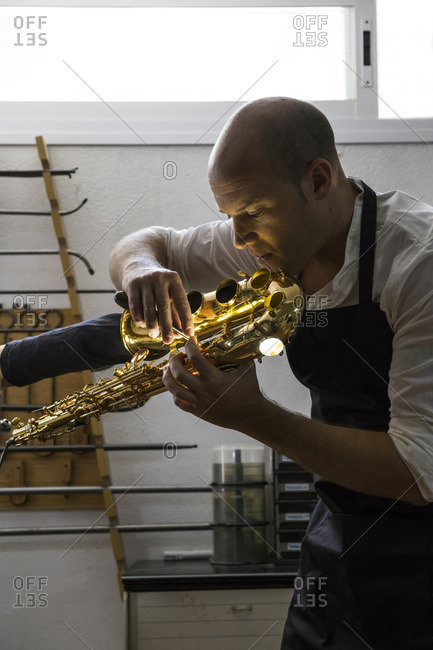 Instrument maker using a scraper during a saxophone repair