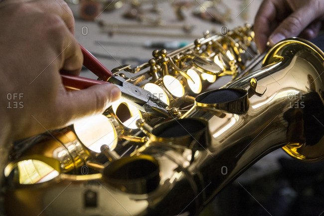 Instrument maker dismounting a saxophone using pliers during a repair