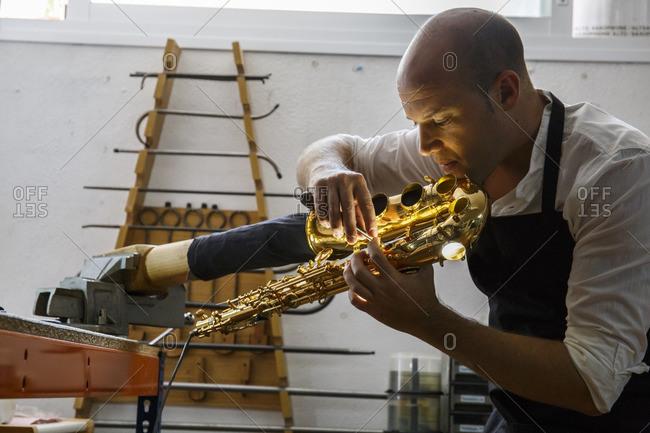 Instrument maker using a scraper during a saxophone repair