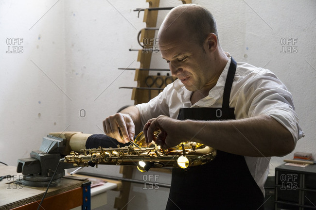 Instrument maker dismounting a saxophone during a repair