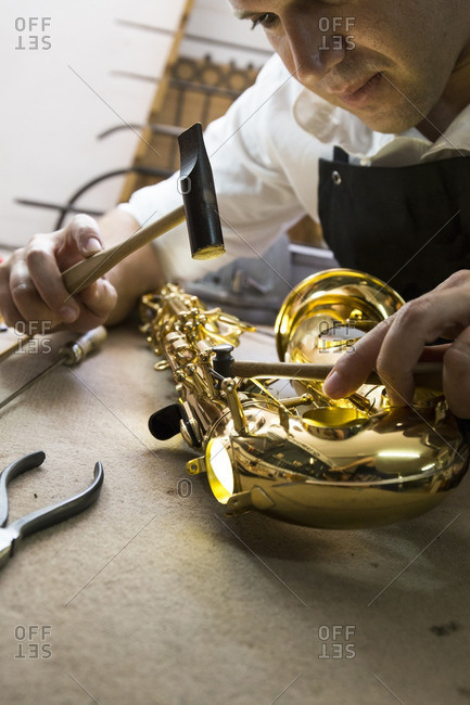Instrument maker using a hammer repairing a saxophone