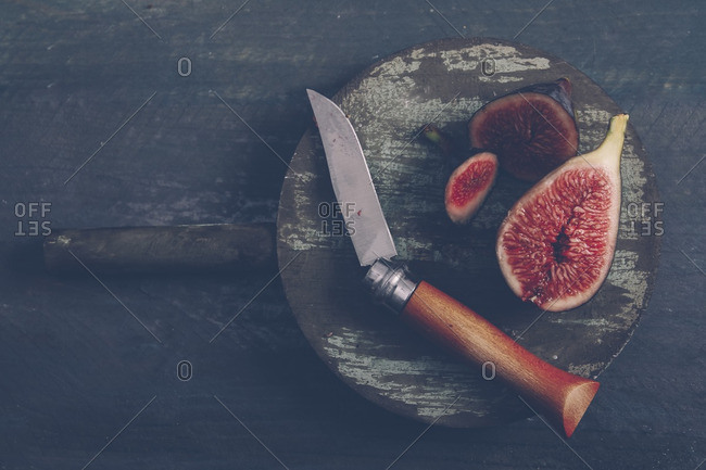 Sliced figs on the wooden board with pocket knife