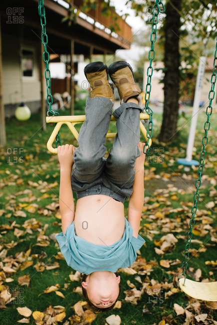 Young boy hanging upside down on rings