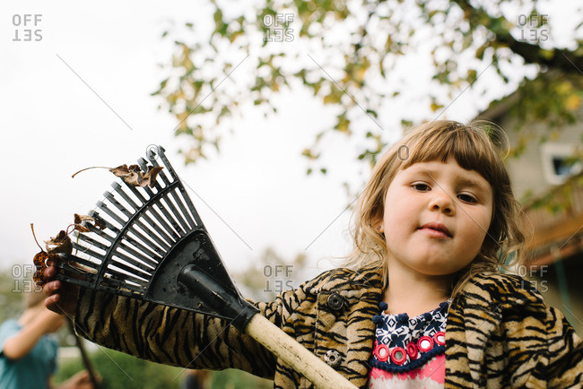 Young girl with rake in autumn