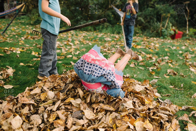 Young girl doing a somersault in a pile of leaves