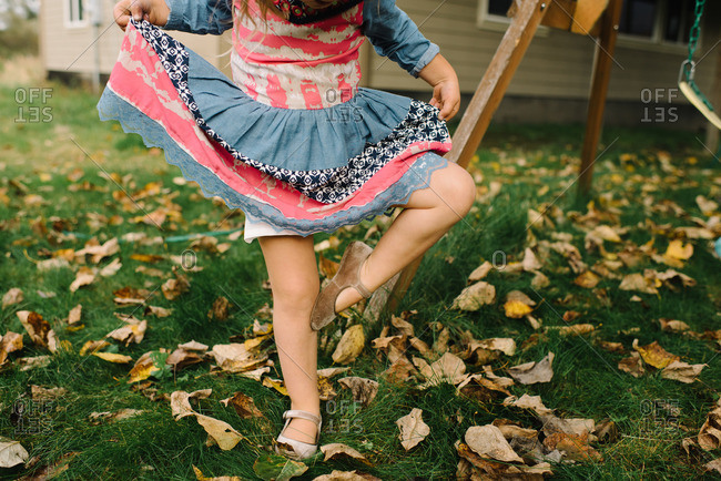 Young girl's legs posed daintily as she holds her dress out