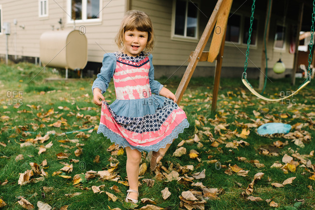 Toddler girl poses while holding out her dress in backyard