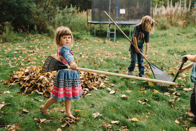Girl dances with rake while her brothers make pile of leaves