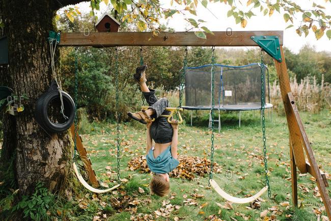 Upside down boy on swing set