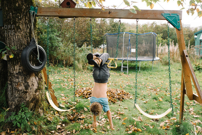 Boy hanging hands free on swing set