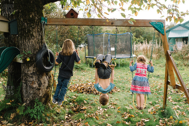 Three siblings playing on swing set