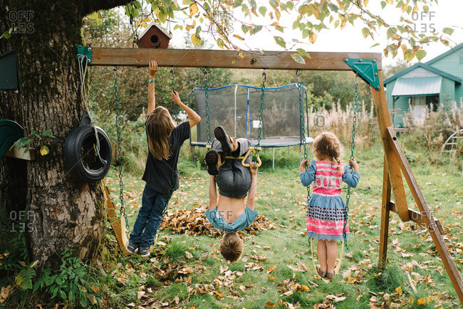 Three young siblings playing on swing set