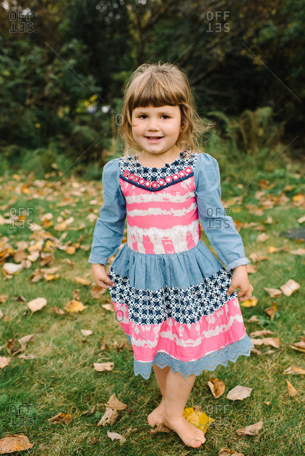 Barefoot young girl in dress in backyard