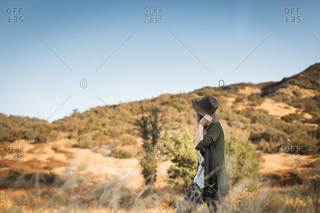 Young woman walking through a field in desert hills