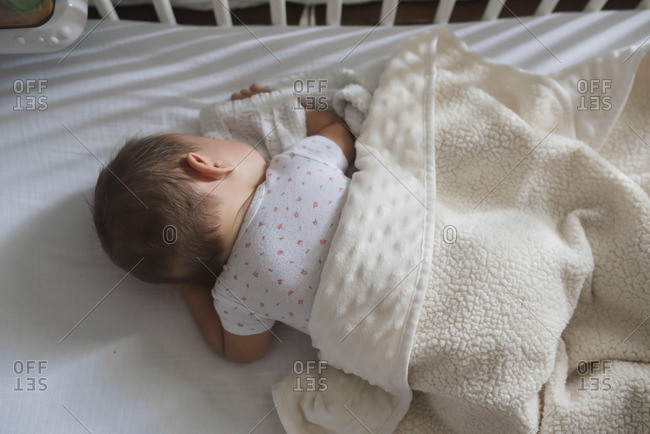 Overhead view of infant sleeping in crib