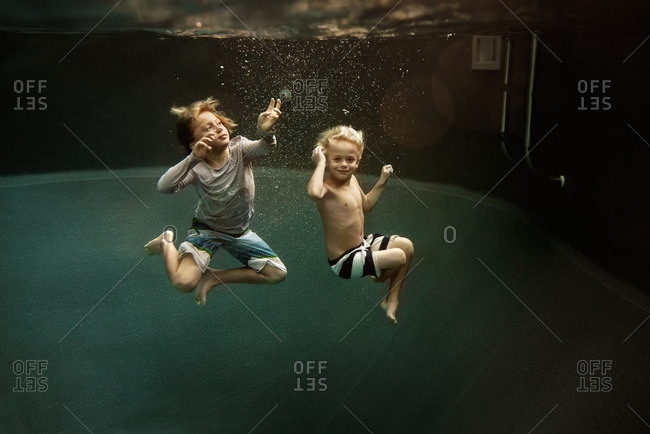 Two kids submerged in pool