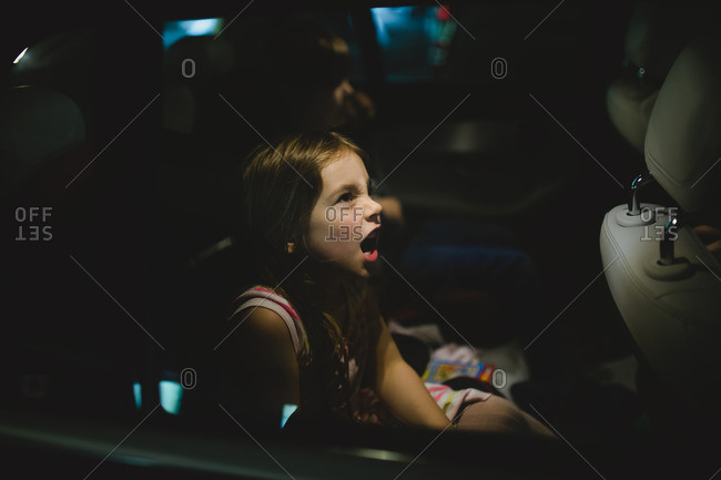 Mad little girl riding in backseat of a car