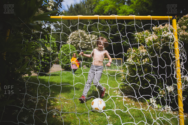 Siblings playing soccer in their backyard