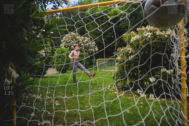 Boy scoring goal in soccer in his backyard